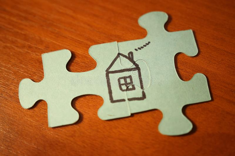 Home concept. House from puzzles on wooden background. Build house. house is painted on puzzles. Pile up puzzles stock photography