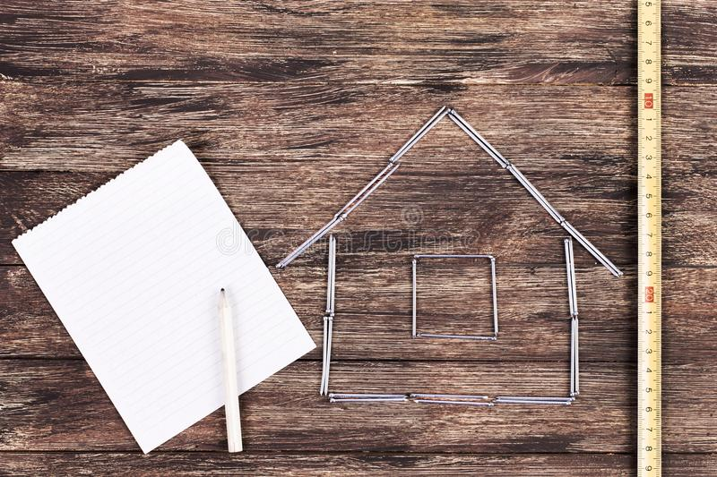 Home concept. Wooden model house on a work table with tools and empty spiral notebook stock photography