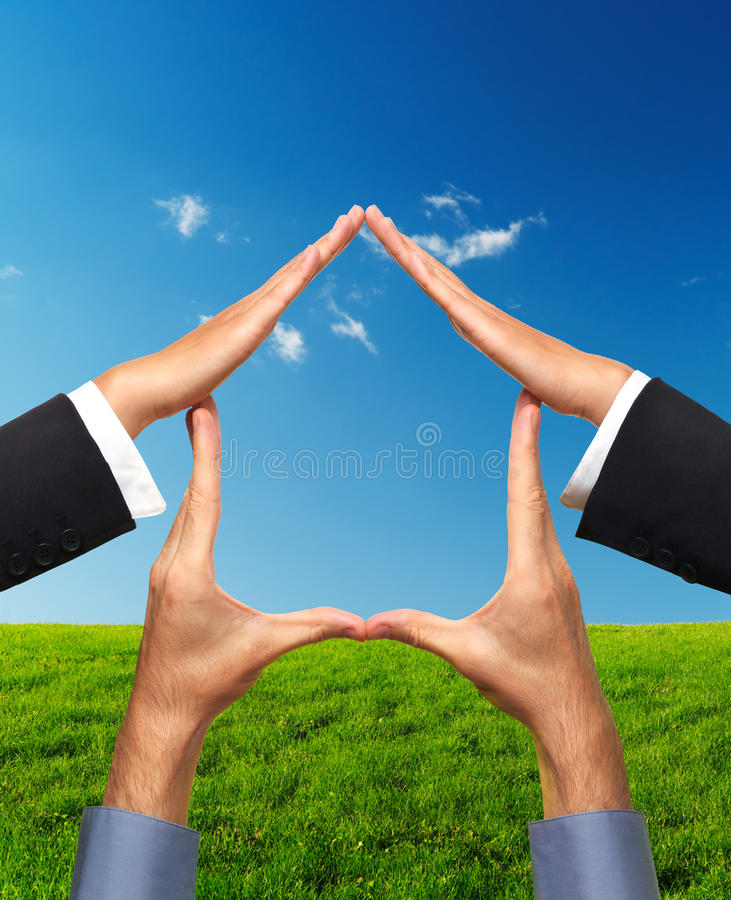 Home Conceptual Symbol Made by Hands. Conceptual house symbol made by hands over bright sunny landscape background. Real estate, housing, construction industry stock image