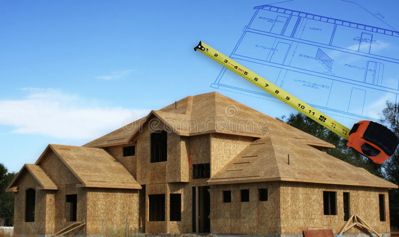 Home Construction. A home under construction with house plans outlines hovering in the sky and a measuring tape royalty free stock photo