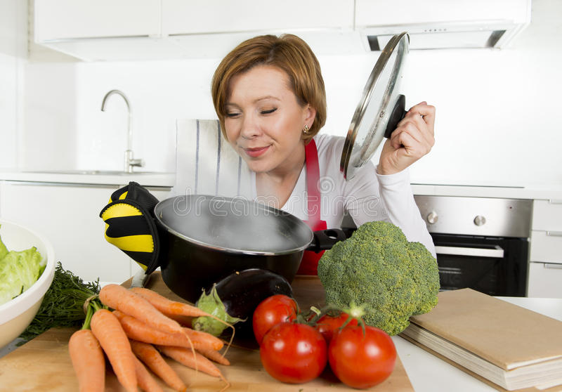 Home cook woman in red apron at domestic kitchen holding cooking pot with hot soup smelling vegetable stew. Young attractive home cook woman in red apron at stock photo