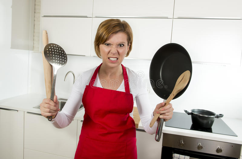 Home cook woman in red apron at domestic kitchen holding pan and household in stress. Young attractive home cook woman in red apron at domestic kitchen holding royalty free stock photo