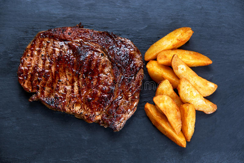 Home Cooked Medium rare grilled Beef steak Ribeye with roasted potato. on blue stone background stock photos