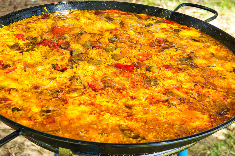 Home cooked Spanish Valencian paella in large flat frying pan. Variety of meats, vegetables, rice, tomato sauce. royalty free stock image