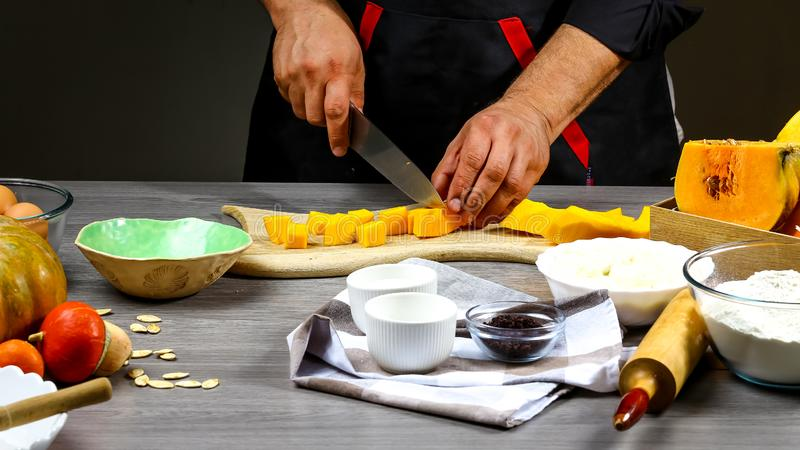 Home cooking American pumpkin pie with cheese and cooking ingredients with a cutting board on the background of a wooden table,The stock image