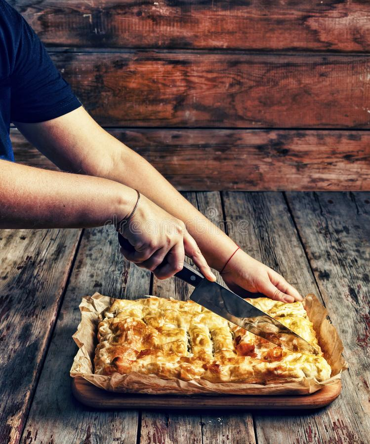 Home cooking. Women`s hands cut homemade pie with stuffing. Celebrating the Day of Independence of the United States. Close up stock image