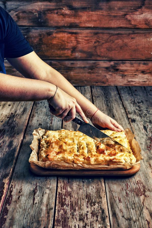Women`s hands cut homemade pie with stuffing. Celebrating the Day of Independence of the United States.Home cooking. Home cooking. Women`s hands cut homemade royalty free stock photos