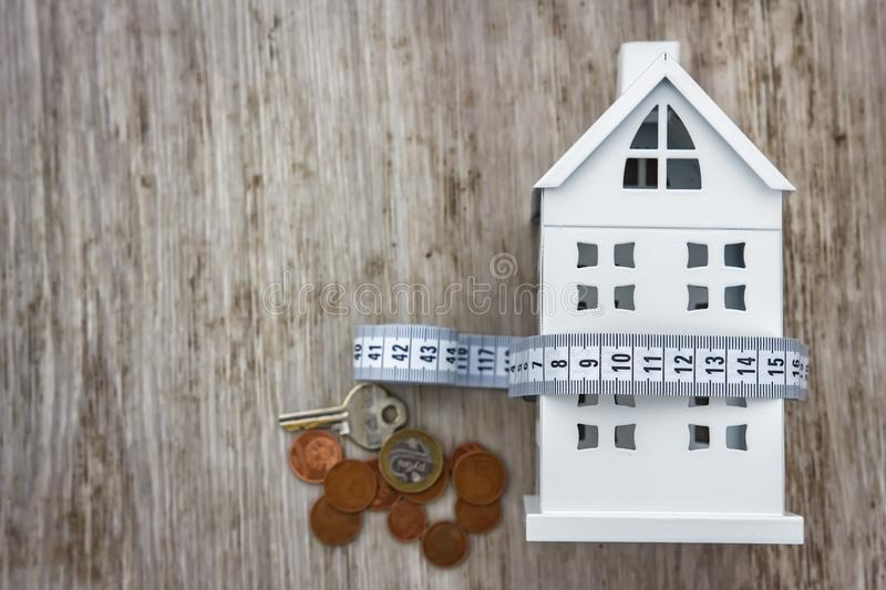 Home costs concept. House, money coins and measuring tape on wooden background. Maintenance costs. Payment for utility bills. royalty free stock image