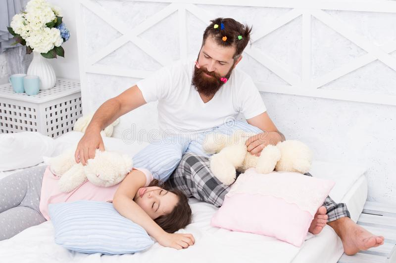 Home day. happy morning together. good night. funny pajama party. small girl with bearded father in bed. weekend at home stock photos