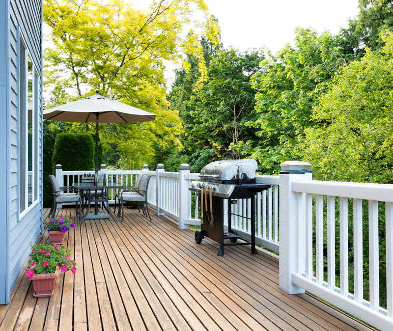 Home deck and patio with outdoor furniture and BBQ cooker with b. Clean outdoor cedar wooden deck and patio of home with BBQ cooker and bottled beer stock photo