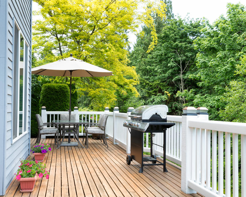 Home deck and patio with outdoor furniture and BBQ cooker. Clean outdoor cedar wooden deck and patio of home during daytime stock images