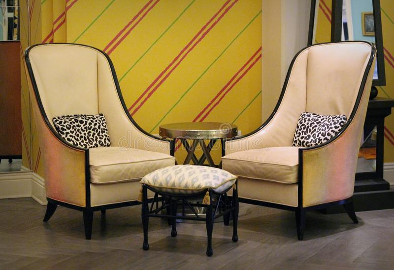 Home Decor: Pair of chairs with table and pillows. Two chairs with pillows and side table with yellow wall paper decoration. Home decor interior design stock photo
