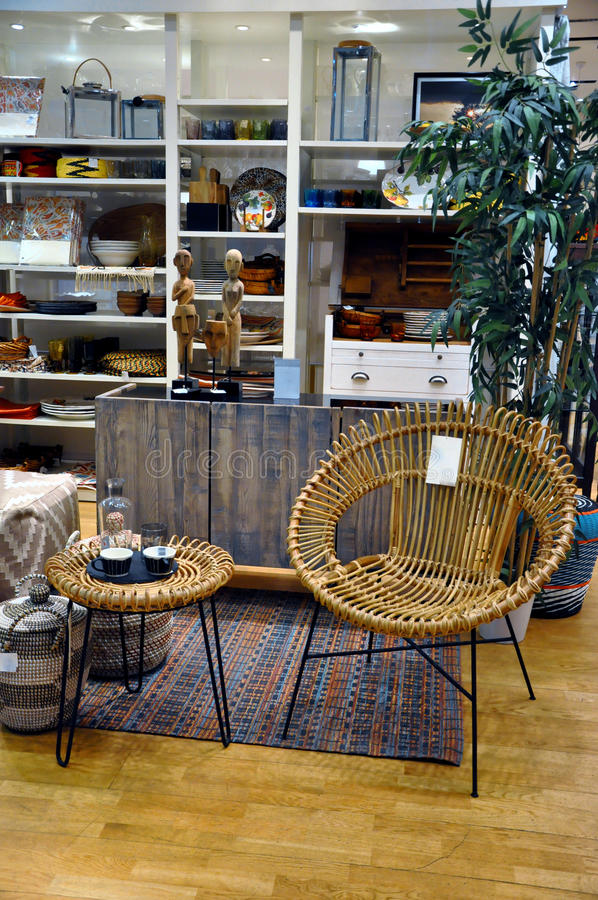 Home decor store. Chair made of rattan and small table in home decor store stock photo
