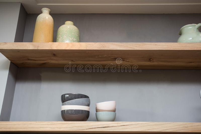 Home decor - various neutral colored vases wooden shelf against grey wall. royalty free stock photos