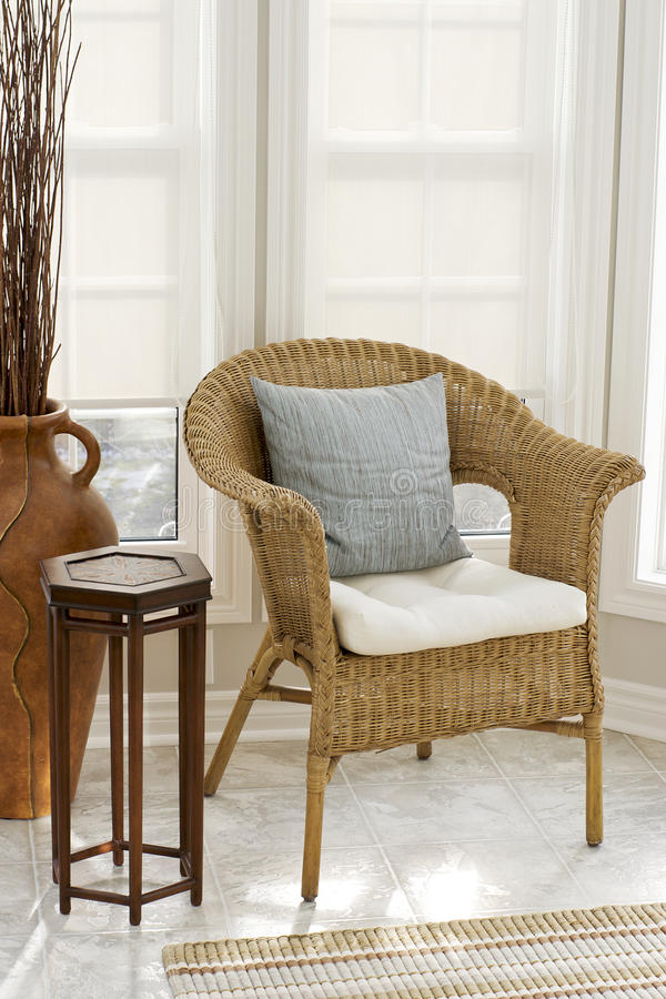 Home Decor - Wicker Chair in Sun room. Clean lines and fresh colours are an invitation to relax and have a seat in this sun room. Roller Blinds help to keep the royalty free stock images