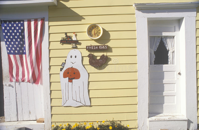 Home decorated for Halloween. Halloween decorations and an American flag on a yellow wooden house royalty free stock photo