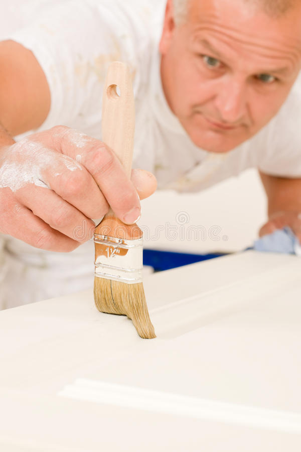 Home decorating mature man painting door brush. Home decorating mature man painting white door with paint brush royalty free stock image