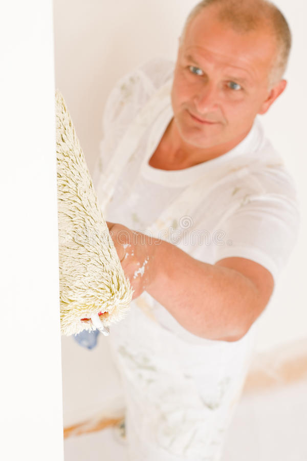 Home decorating mature man painting wall roller. Home decorating mature man painting white wall with paint roller stock images