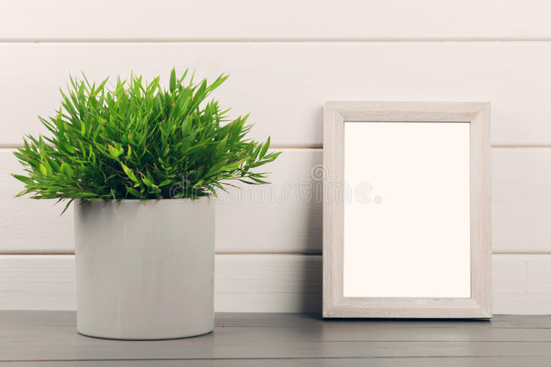 Home decoration - blank picture frame and flower pot on wooden t stock photos
