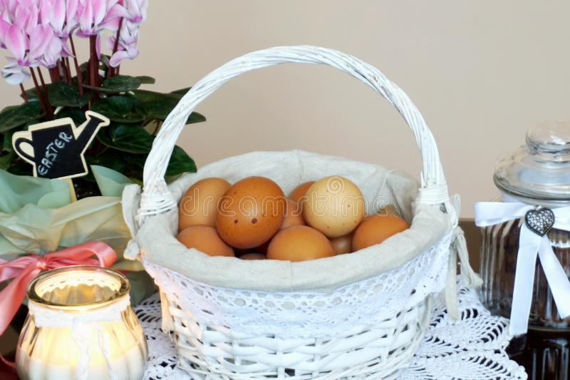 Home decoration for Easter celebration with basket full of fresh chicken eggs in the center stock image