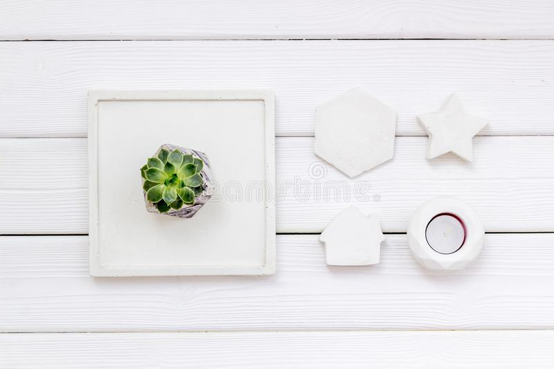 Modern design of work desk with plant, candle, house and star figures on white wooden background top view. Home decoration. Modern design of work desk with plant royalty free stock photography