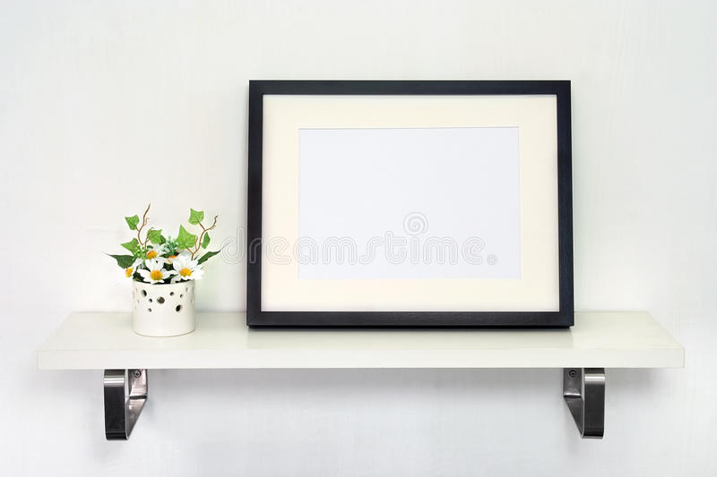 Home Decoration Photo Frame. Potted daisies and a black photo frame on white shelf against a white wall royalty free stock photo