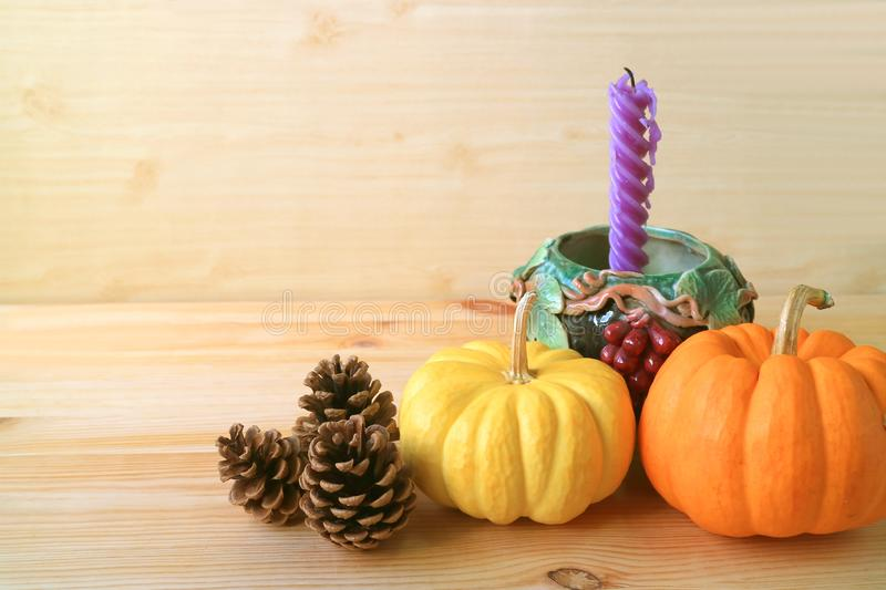Home Decorations with Vibrant Color Ripe Pumpkins, Natural Pine Cones and Purple Candle in Grape Motif Holder. Halloween holidays stock photo