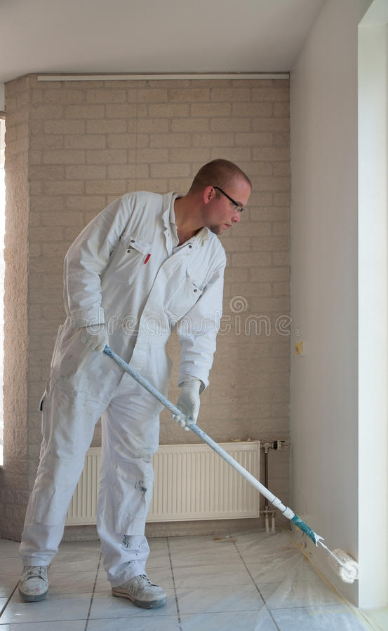 Home decorator painting wall with a roller. Home decorator painting a wall white with a long roller stock photography
