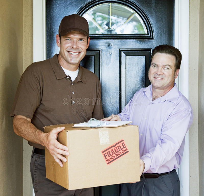 Home Delivery. Delivery man hands package to satisfied customer stock image