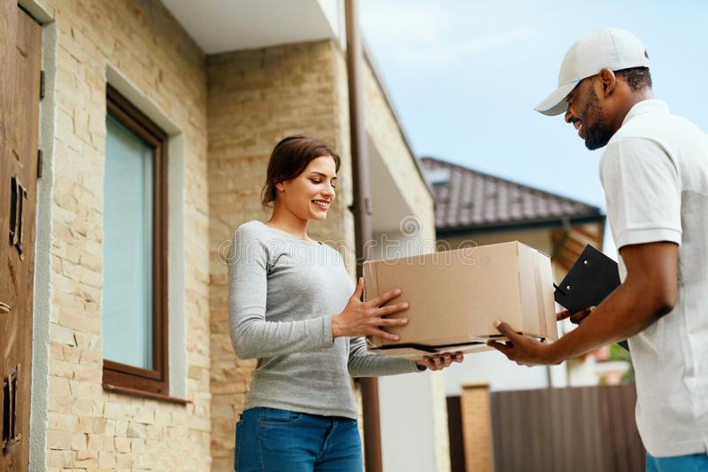 Home Delivery. Courier Delivering Package To Client royalty free stock images