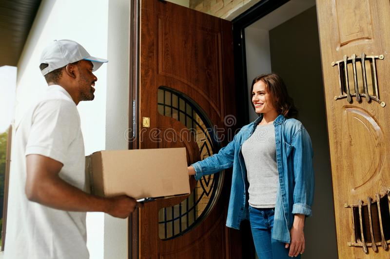 Home Delivery. Courier Delivering Package To Client. Smiling Woman Receiving Box From Delivery Man Near Door. High Resolution stock photography