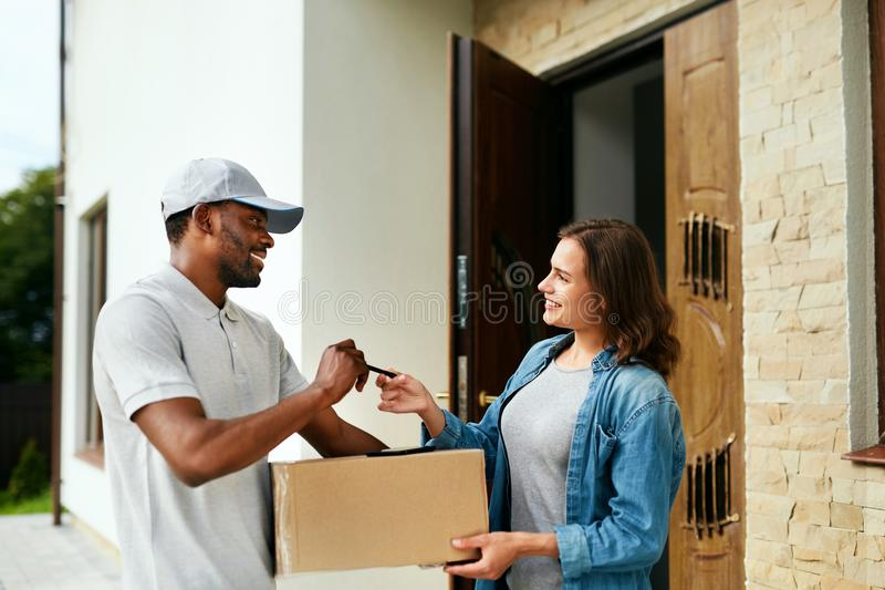 Home Delivery. Courier Delivering Package To Client. Smiling Woman Receiving Box From Delivery Man Near Door. High Resolution royalty free stock photo