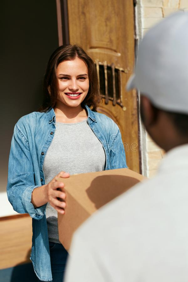 Home Delivery. Courier Delivering Package To Client. Smiling Woman Receiving Box From Delivery Man Near Door. High Resolution stock photo
