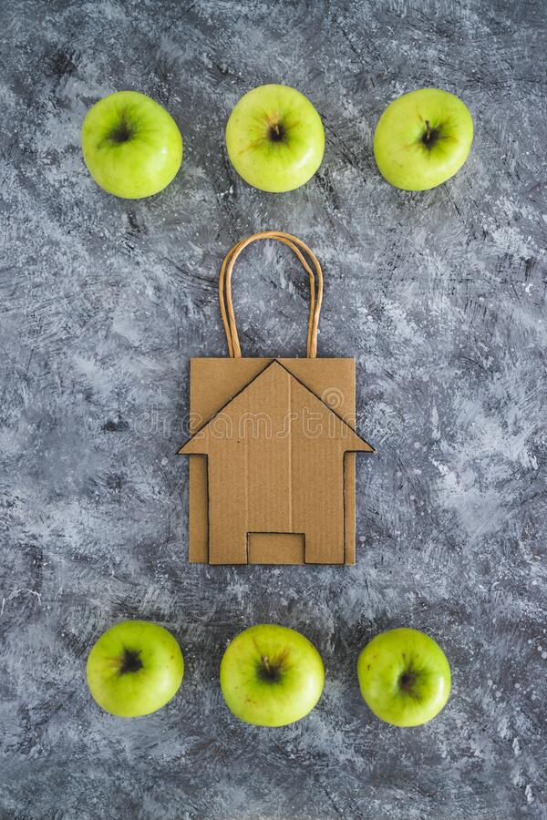 Home delivery and groceries shopping concept, shopping bagwith house icon among apples. Symbol of healthy nutrition royalty free stock images