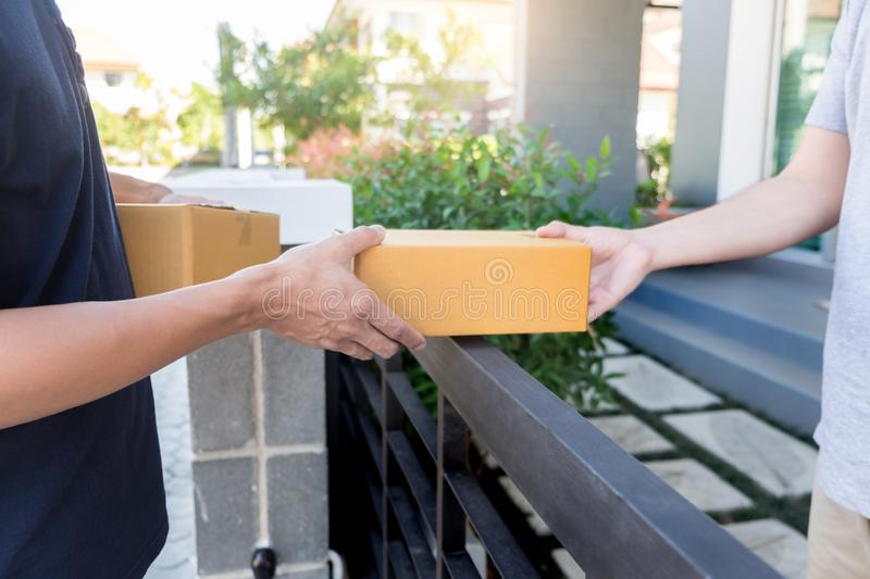 Home delivery service delivers package at home and woman receiving by signing for online shopping order.  stock photo