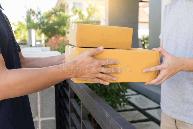 Home delivery service delivers package at home and woman receiving by signing for online shopping order.  stock image