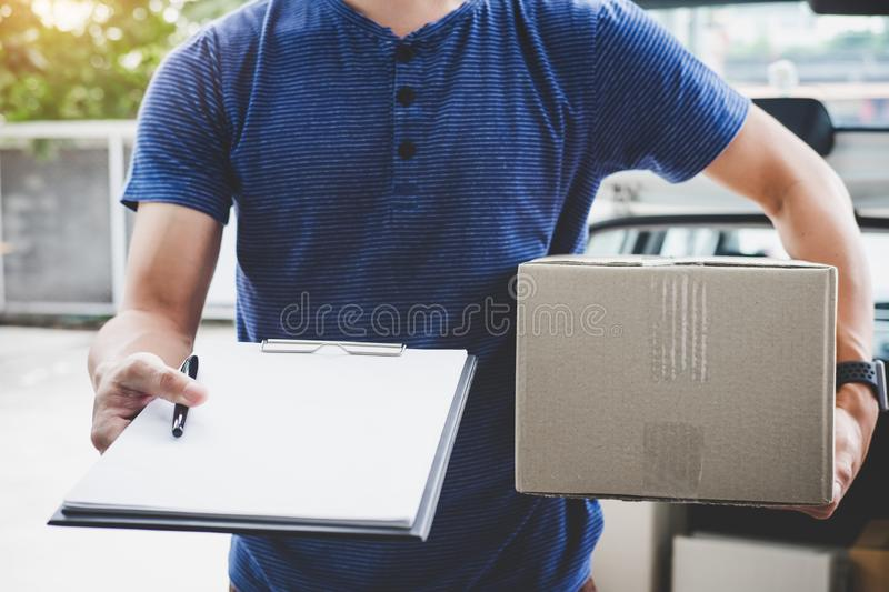 Home delivery service and working with service mind, deliveryman with boxes standing by in front of the customer house doors and. Holding clipboard royalty free stock photos