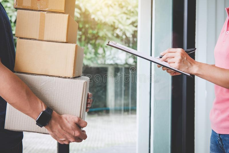 Home delivery service and working with service mind, Woman customer signing and receiving a cardboard boxes parcel from stock photography
