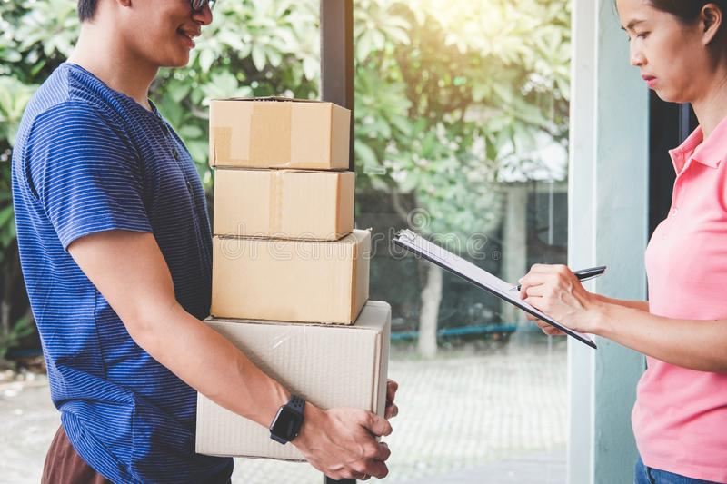 Home delivery service and working with service mind, Woman customer signing and receiving a cardboard boxes parcel from royalty free stock photos