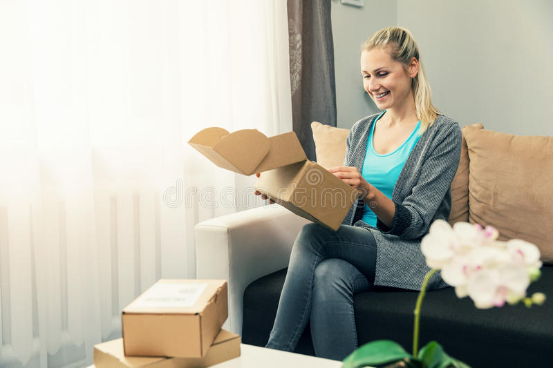 Home delivery - smiling young woman opening cardboard box royalty free stock images