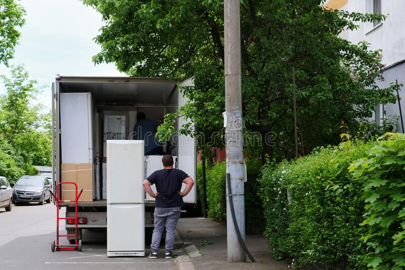 Home delivery workers unload household appliances from a van royalty free stock photo