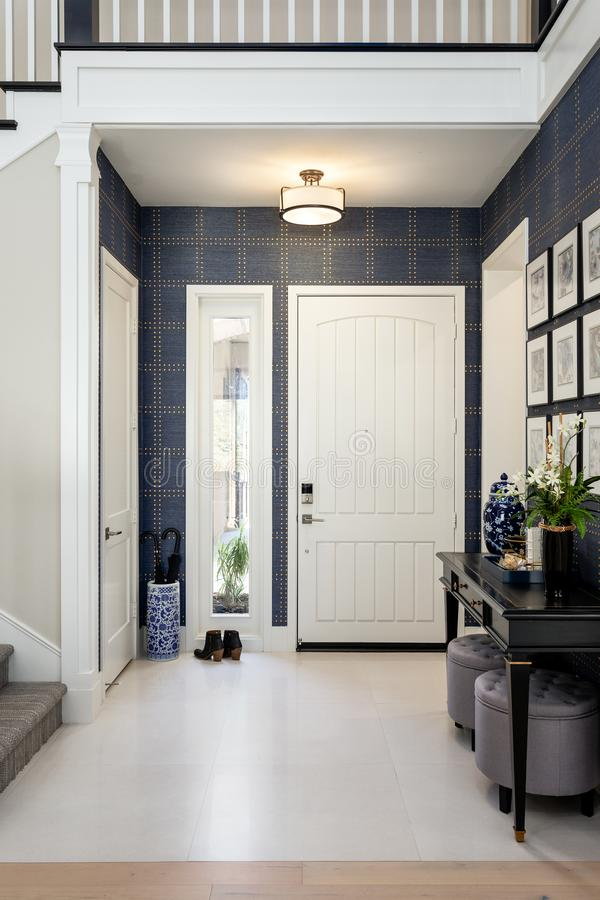 Home design remodel entryway with wallpaper. Front door, shoes, stairs stock photography