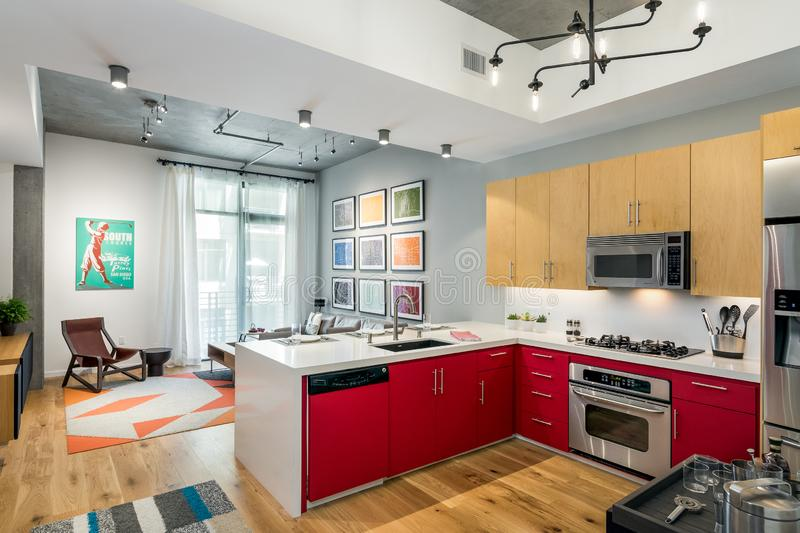 Home design remodel kitchen and living space with red. Cabinets, wood flooring royalty free stock photos