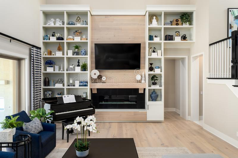 Home design remodel living space with grand piano. Wood flooring, tall built in shelving royalty free stock image