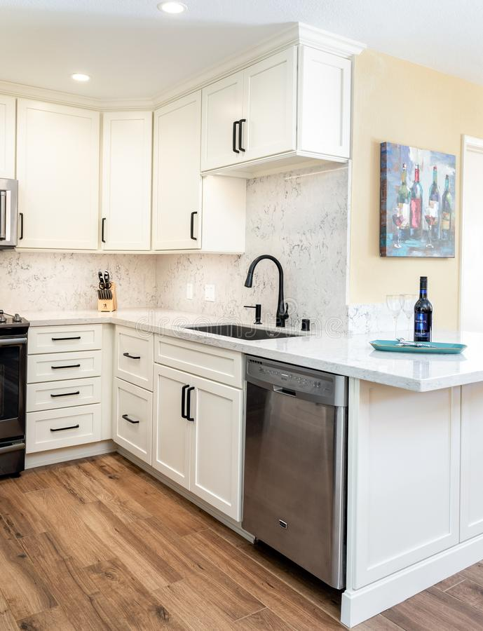 Home design remodel small kitchen with white cabinets. Wine and glasses, wood flooring royalty free stock photography