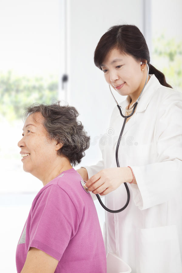 Home Doctor Measuring Senior Woman Blood Pressure Stock Photo