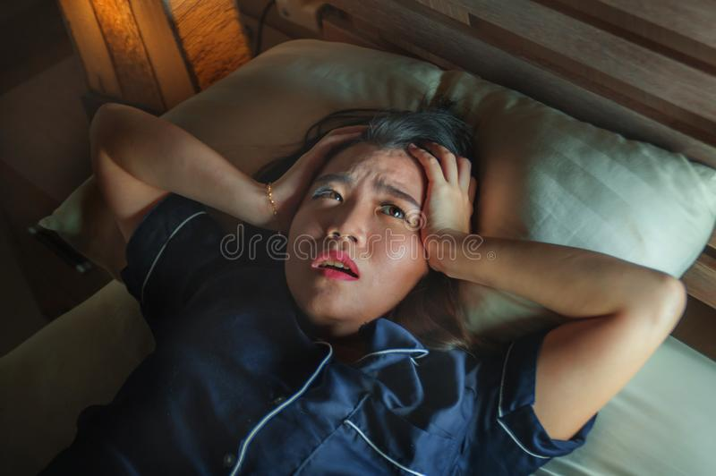 Home dramatic lifestyle portrait of young beautiful sad and depressed Asian Korean woman awake in bed late night suffering anxiety royalty free stock photography