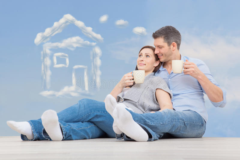 Home dreamers. Couple dreaming of new home sitting on floor