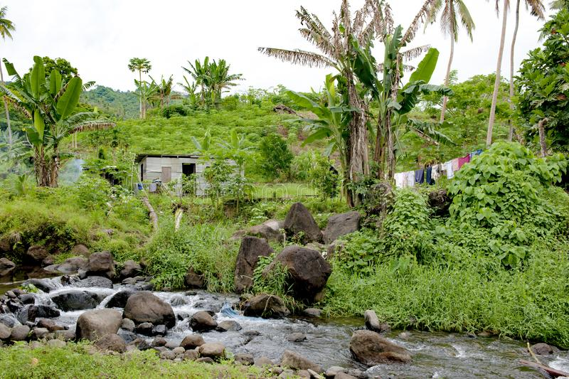 Home at the edge of the rainforest, Fijian house in tropical garden with. Typical house on Somosomo, Fiji, with beautiful tropical garden and creek stock photography