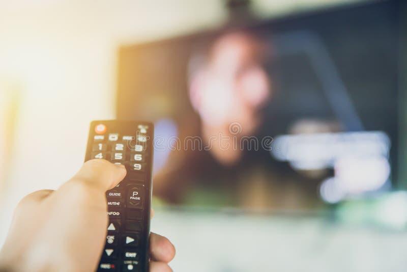 Home entertainment telecomando astuto della tenuta TV della mano con un fondo della sfuocatura della televisione immagine stock